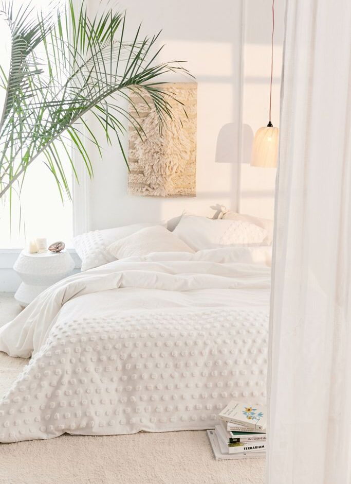 WHte neutral Bohemian bedroom with macrame tapestry, fern and hanging pendant light, IMAGE: via Urban Outfitters.