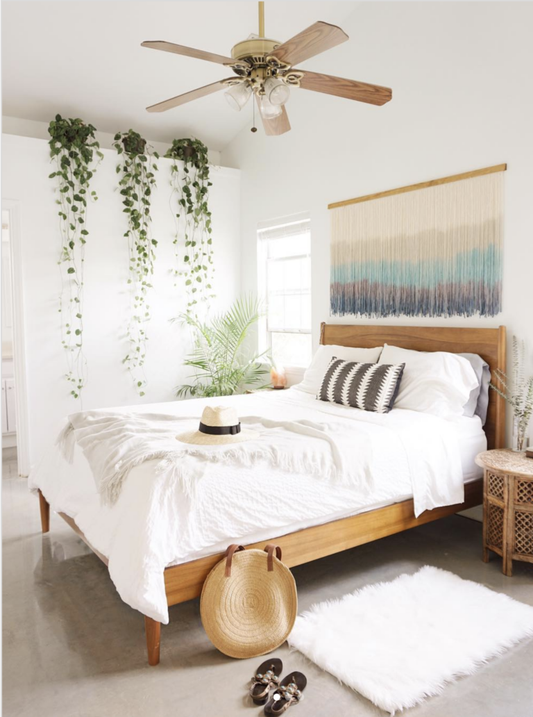 Modern Bohemian bedroom with wall tapestry and hanging plants, IMAGE: via @theboholoft on Instagram. Stylish Boho Bedside Lamps and Lighting Options.