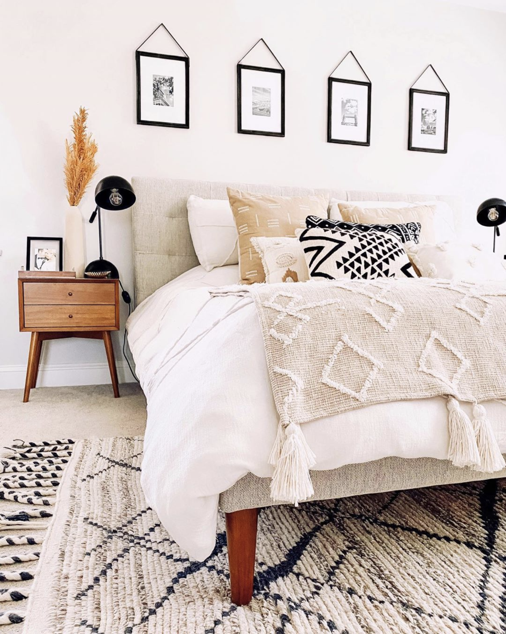 Boho-Chic bedroom with tribal/aztec rug and pillows, Mid-century modern nightstand, IMAGE: via @homedesignbyjaime on Instagram.