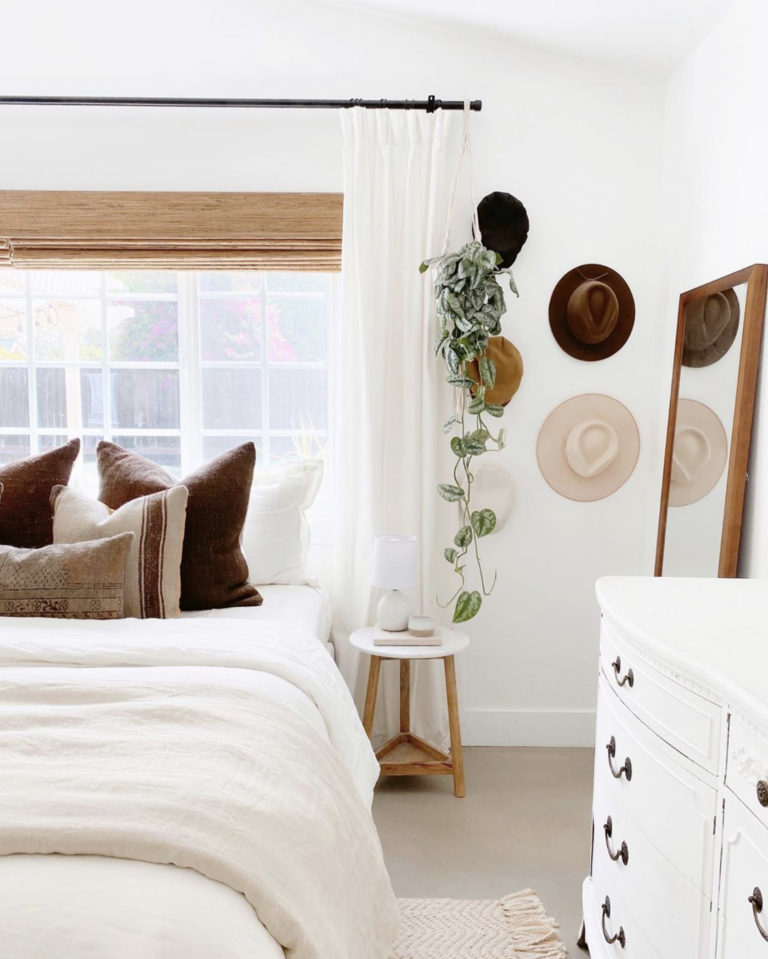 Modern minimal Bohemian bedroom in white/neutral palette with hats on the wall, IMAGE: via @theressnowplacelikehome on Instagram.