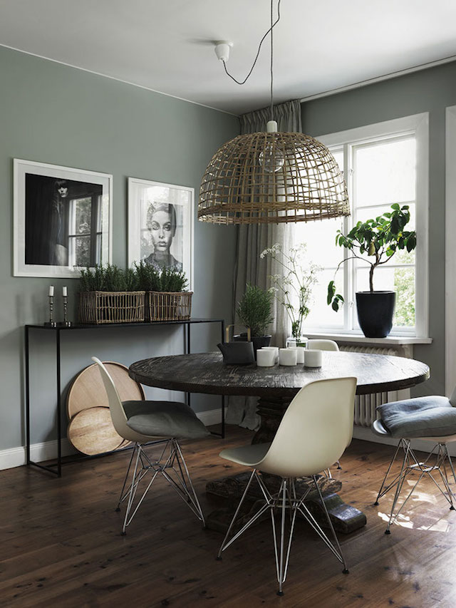 Image via Jonas Ingerstedt Photography, beautiful sage green dining space with round wood pedestal table and oversized rattan pendant light, Mid-Century inspired dining chairs.