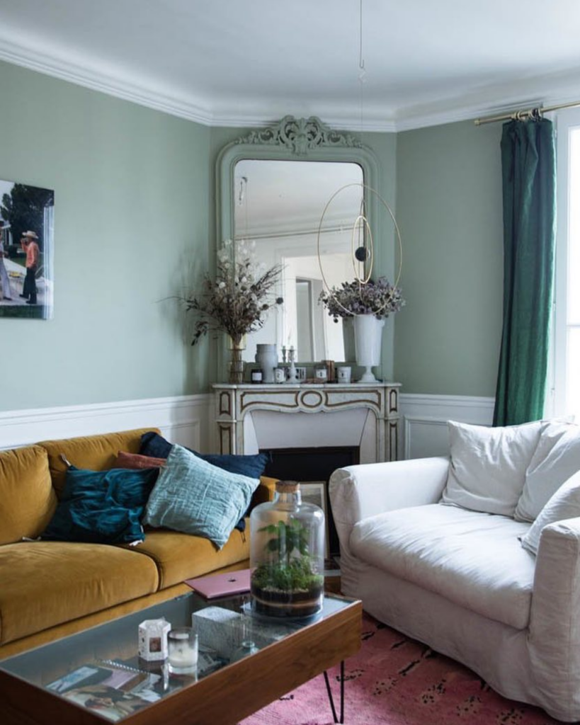 Image via @thesocialitefamily, sage green walls with velvet mustard yellow sofa.