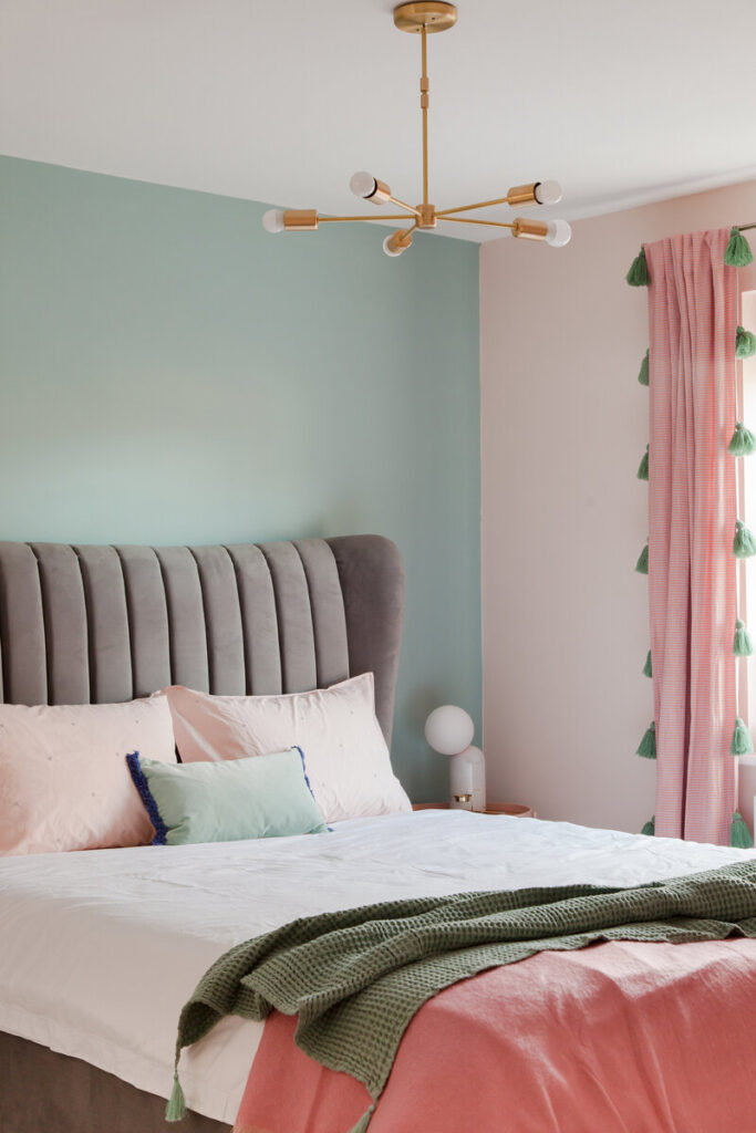 Image via Rukmini Patel Interior Design, mint green accent wall with gray padded headboard and pink tassel curtains.