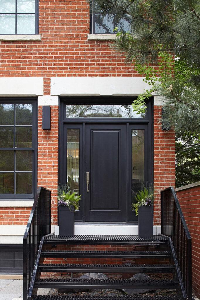 10 Popular Front Door Colors for Brick Houses - Image via Home DSGN, photo by Mike Sinclair, black door