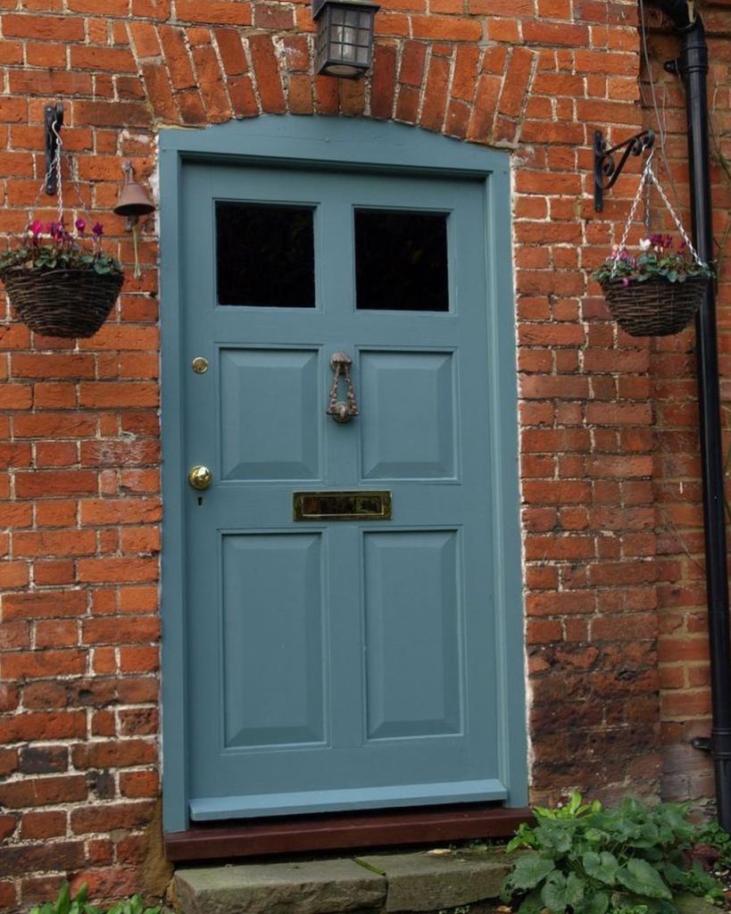 10 Popular Front Door Colors for Brick Houses - Image via @verfbehangmarcovandenberg, blue-gray door