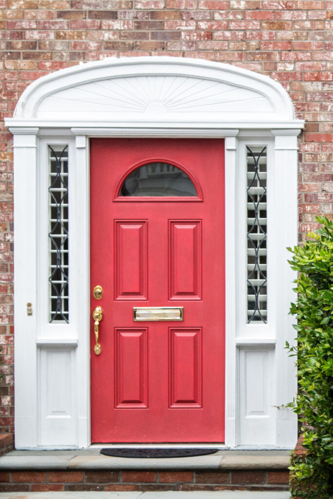 10 Popular Front Door Colors for Brick Houses - Image via Unsplash, by Landon Martin, red door