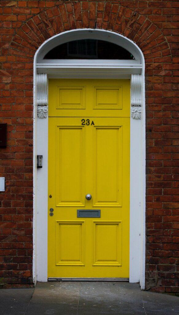 Image via Unsplash, by Samuel Mcgarrigle, yellow door