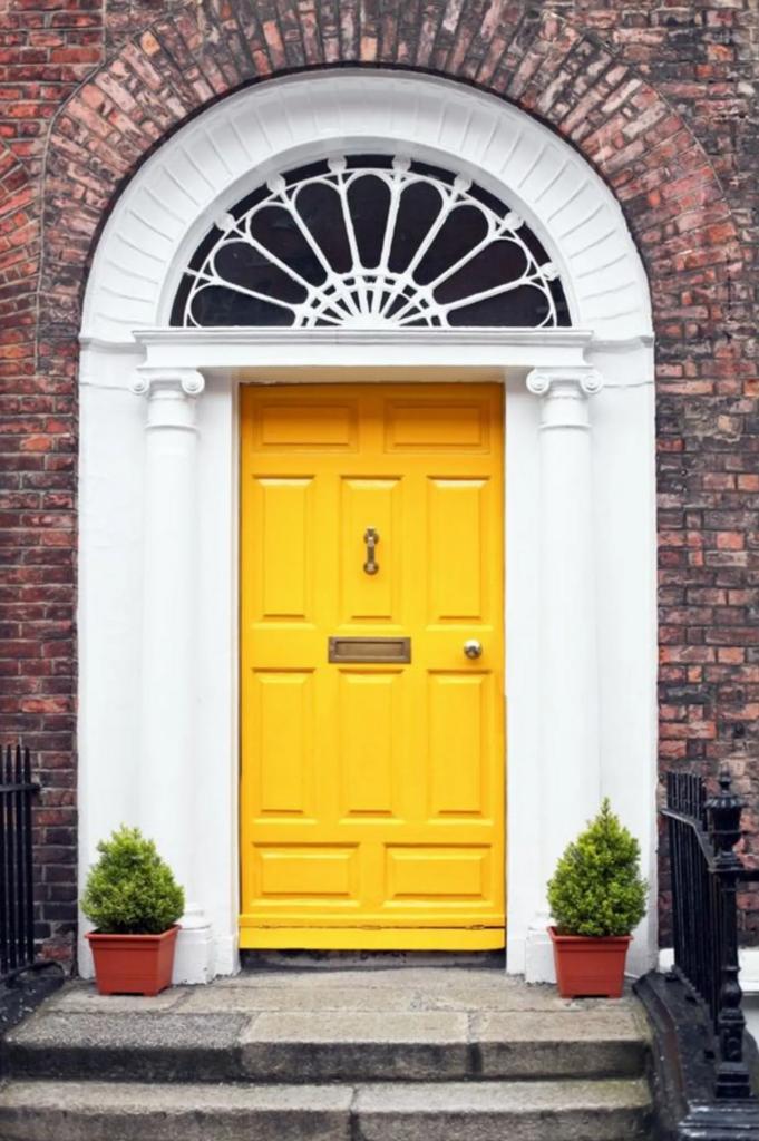 10 Popular Front Door Colors for Brick Houses - Image via House Beautiful, yellow door