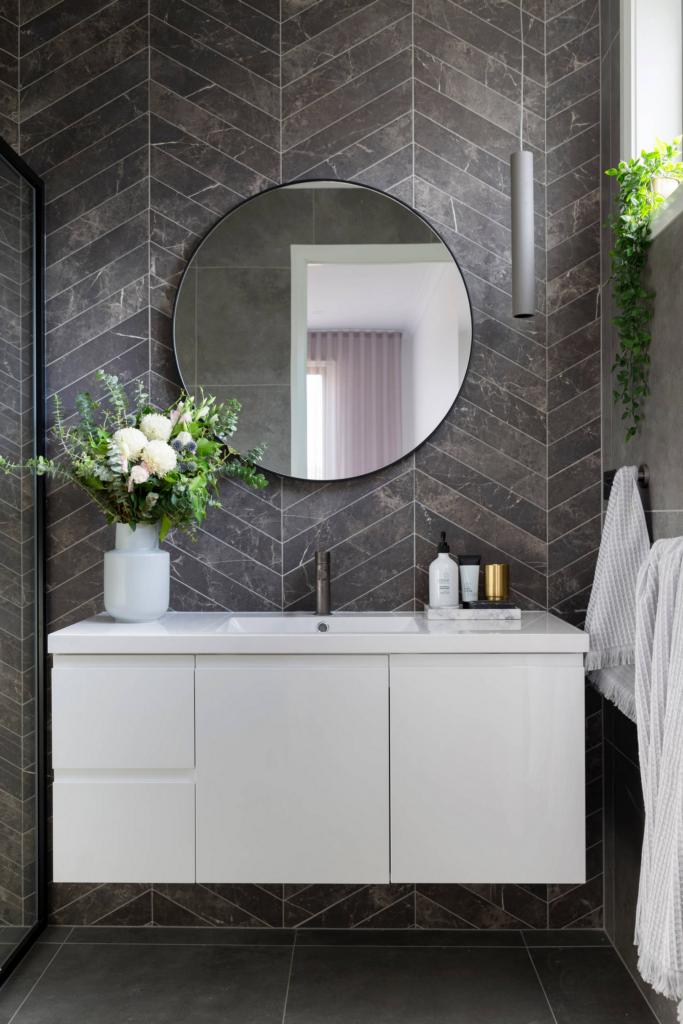 Photo by Hcreations fro Studio Black Interiors via Houzz, dark gray herringbone tile in modern bathroom with round black vanity mirror