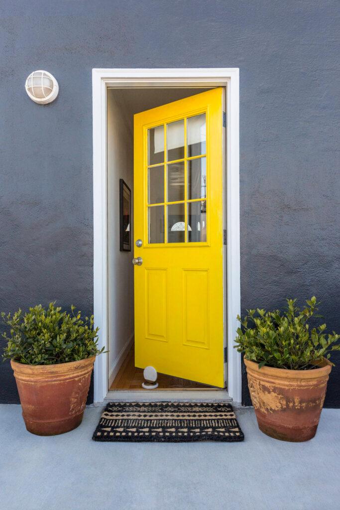 Bright yellow door, gray walls - Photo by Lauren Edith Andersen viaHouzz