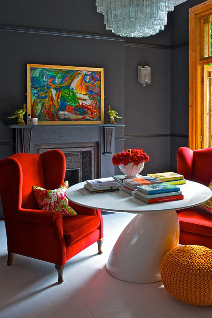 Dark gray sitting room with red velvet wingback armchairs - Image via Frenchy Fancy