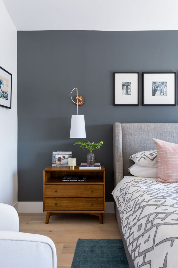 Dark gray accent wall in bedroom - Photo by Amy Bartlam via Rue Daily