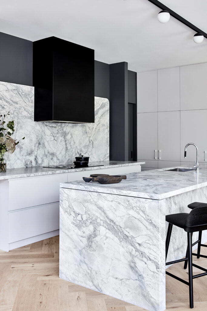 Marble kitchen with charcoal gray walls and black accents - Image via Mim Design